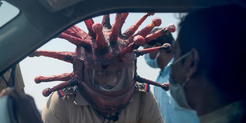 Policista s originální přilbou kontroluje dodržování karantény v indickém městě Čennaí (Profimedia.cz)