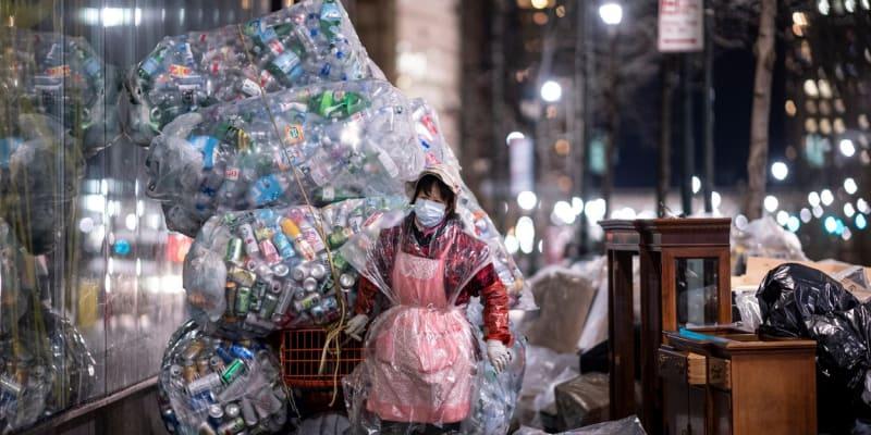 Žena vláčí ulicemi New Yorku obří pytle s plastovým odpadem.