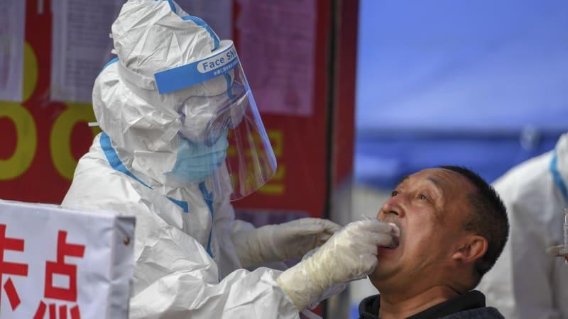 Lékař v čínském městě Šu-lan provádí test pacientovi s podezřením na koronavirus