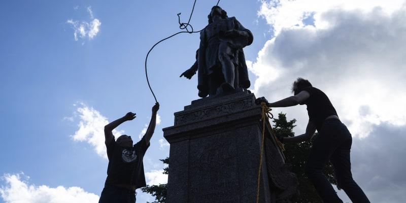 Mike Forcia (vlevo) a další muž se snaží hodit lano na krk sochy Kryštofa Kolumba v americkém městě St. Paul. Nakonec se jim to podařilo a dav sochu svrhl.