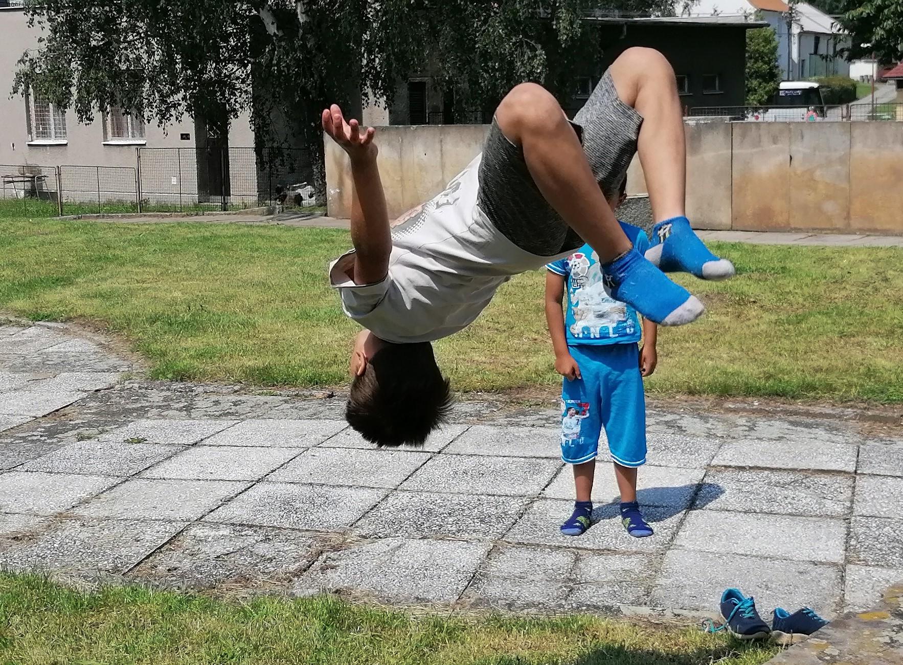 Děti trénují přemety na betonových podstavcích pomníku Osvobození.