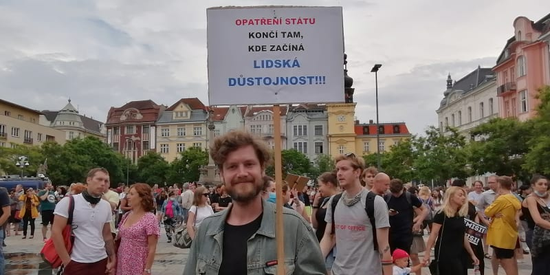 Muž s cedulí vyjadřuje svůj názor na ostravské demonstraci.