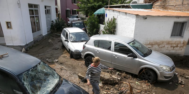 Žena prochází kolem poškozených aut v obci Politika na ostrově Evia.