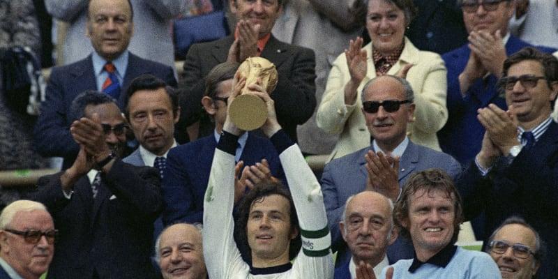 Franz Beckenbauer jako kapitán německé reprezentace drží nad hlavou trofej pro mistry světa z roku 1974. Vpravo brankář Sepp Maier.