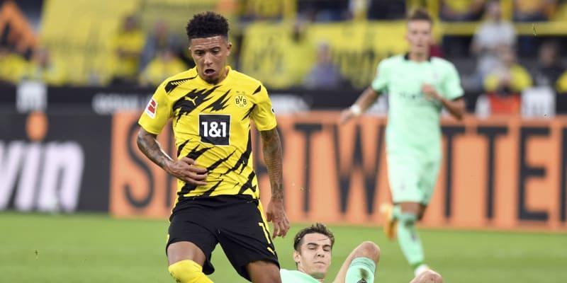 Jadon Sancho z Borussie Dortmund uniká Florianu Neuhausovi z Borussie Mönchengladbach v úvodním utkání německé fotbalové bundesligy ročníku 2020–2021.