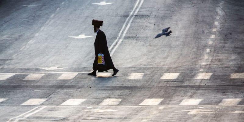 Ortodoxní žid přechází prázdnou ulici během prvního dne třítýdenního uzavření v izraelském Bnej Braku.