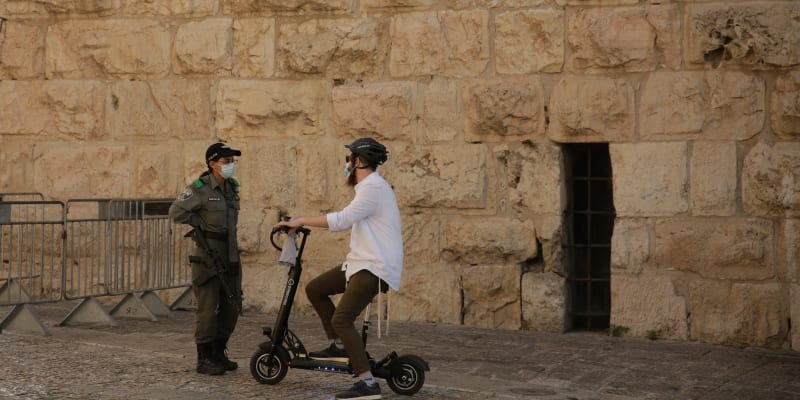 Izraelský příslušník pohraniční policie hovoří s židovským mužem na elektrickém skútru na kontrolním stanovišti u Jaffské brány ve starém městě Jeruzaléma.