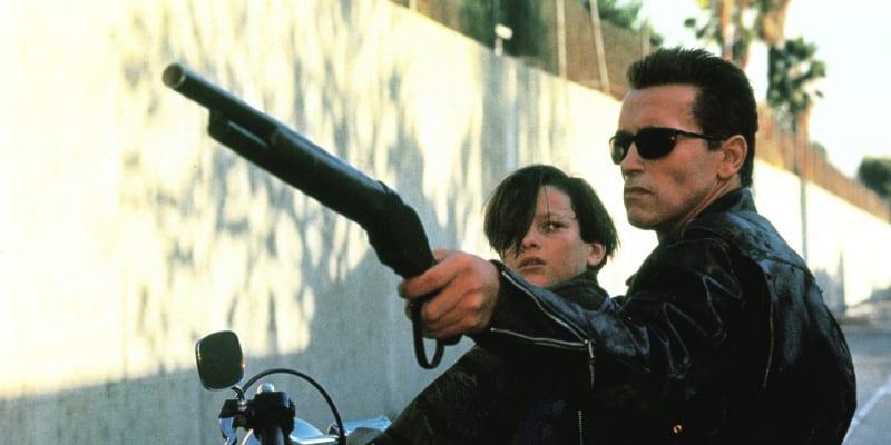 Terminátor 2: Den zúčtování. Arnold Schwarzenegger v jedné ze svých nejslavnějších rolí vůbec. Zde zachraňuje Johna Connora v podání herce Edwarda Furlonga před útokem terminátora T-1000.