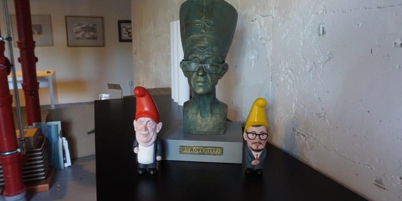 """Při vstupu na výstavu návštěvníky kromě personálu """"přivítá"""" bysta Agrofertiti, která vypadá jako ze starověkého Egypta a doplňují ji  dva trpaslíci. Bysta paroduje premiéra Andreje Babiše, zatímco trpaslíci znázorňují prezidenta Miloše Zemana a jeho mluvčího Jiřího Ovčáčka."""