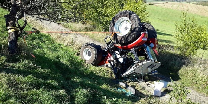 Traktor zůstal převrácený na střeše.
