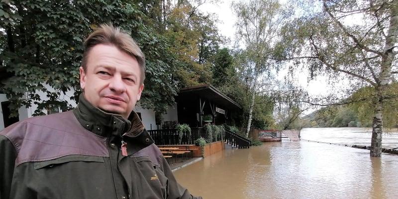Živnostník Jiří Zapletal před zatopenou hospodou Loděnice u řeky Opavy v Děhylově