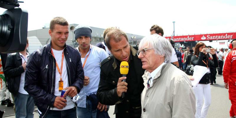 Kai Ebel (uprostřed) zpovídá bývalého šéfa formule Bernieho Ecclestona. Vlevo přihlíží fotbalový mistr světa Lukas Podolski.