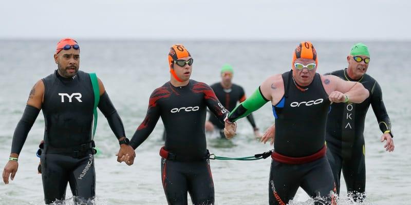 Chris Nikic (uprostřed) a jeho pomocník Daniel Grieb (vpravo) po plavání při Ironmanu na Floridě.