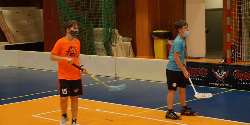 Mladí florbalisté klubu Olymp Florbal při tréninku, který vzhledem k vládním opatřením musí absolvovat v rouškách.