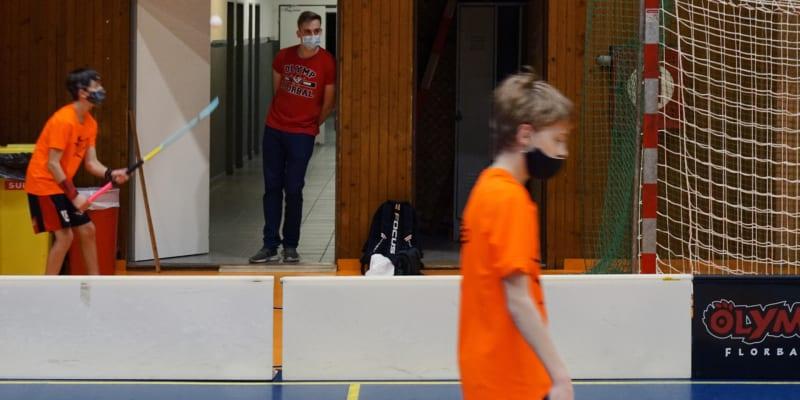 Trenéři klubu Olymp Florbal sledují trénink svých svěřenců z chodby, aby neporušili vládní nařízení o počtu účastníků tréninku v hale.