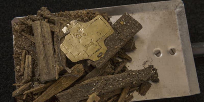 """Trosky dřevěného relikviáře se zlatou destičkou zdobenou tepáním (kříž a písmena """"IR""""). Archeologové objevili v milevském klášteře na Písecku schránku s odseknutou částí hřebu z Pravého kříže. Jedná se o jednu z nejvzácnějších křesťanských relikvií (zdroj: PR/Martin Frouz)"""