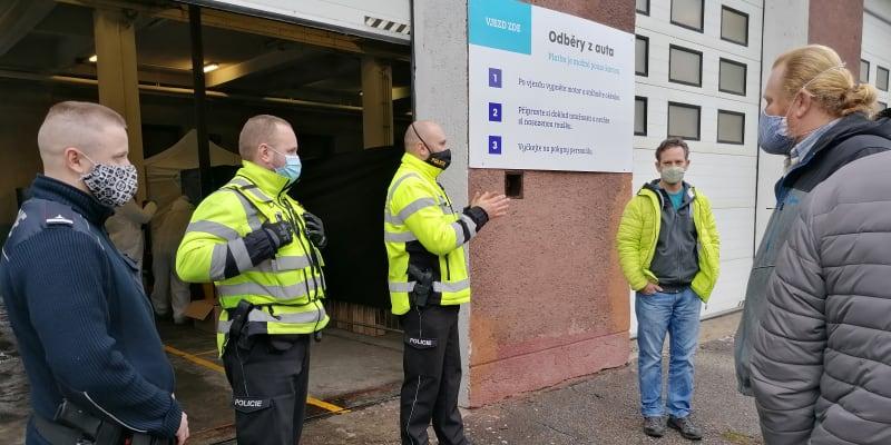 Policie vysvětluje nervózním klientům, že tohle odběrové místo bude znova otevřeno až  27. prosince.  Zřejmě už nepřijdou, stát je zklamal.