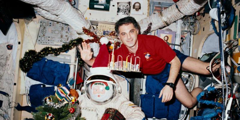 Astronaut NASA David A. Wolf se svou menorou a dreidlem na oslavu Chanuky v roce 1997.