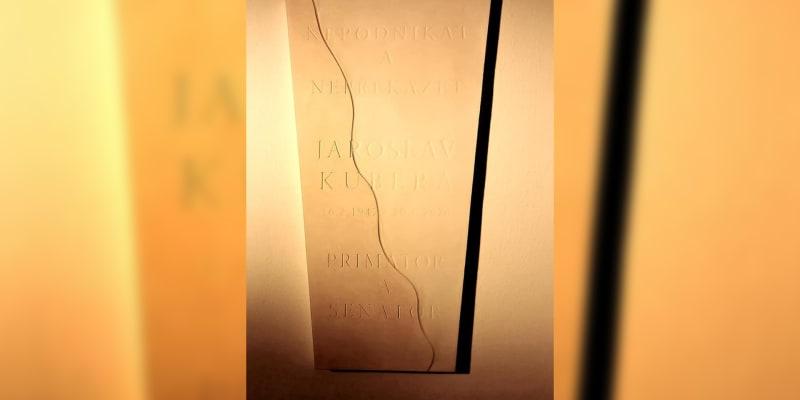 Nepodnikat a nepřekážet bylo podle Hanzy nejčastějším Kuberovým heslem. Nápis je na reliéfu před kanceláří, kde Kubera úřadoval.