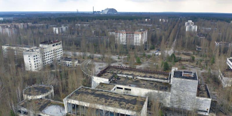 Město duchů Pripjať prorůstající vegetací, na obzoru sarkofág pokrývající vybuchlý reaktor