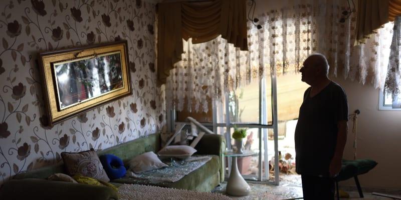 Izraelec obhlíží svůj byt poté, co budovu zasáhl šrapnel z rakety.