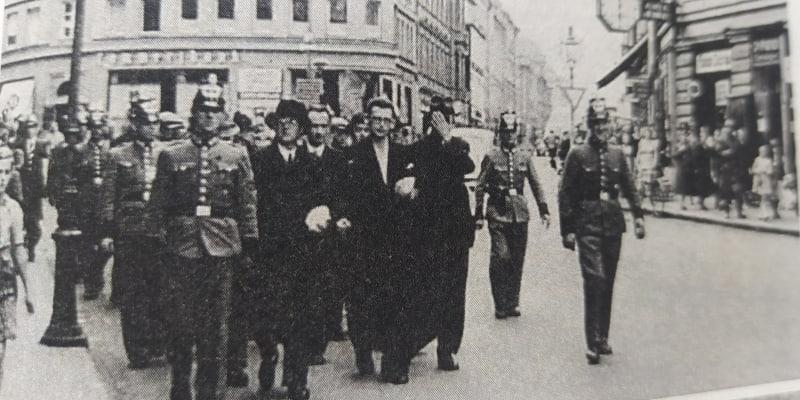 Podzim 1938, nově ustavená Říšská župa Sudety. Říšská policie právě odvádí skupinu zejména místních Němců zatčených pro jejich různorodý antifašistický charakter – Cheb (repro foto z knihy V. Bružeňáka Ve stínu Krušných hor).