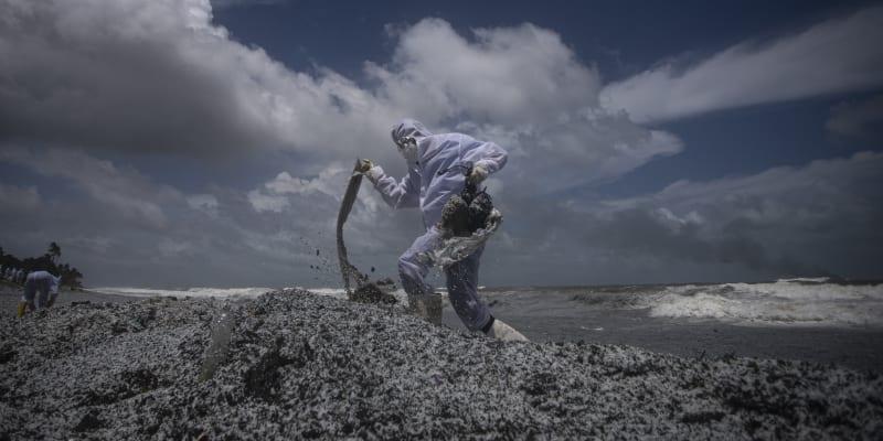 Námořníci se snaží odklidit z pláže kontaminovaný odpad.