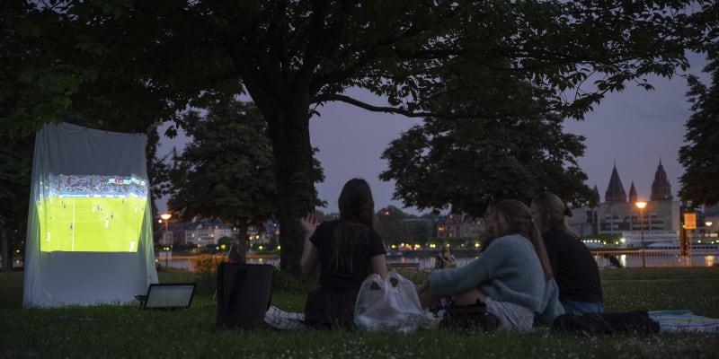 """I takto se dá sledovat fotbalové Euro v době koronaviru. Velké veřejné projekce jsou zakázané, a tak ženy v německém městě Wiesbaden """"pustily"""" fotbal na prostěradlo v parku."""