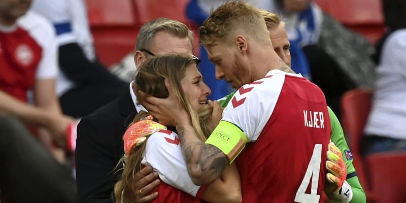 Dánský kapitán Simon Kjaer utěšuje u postranní čáry Sabrinu Kvistovou Jensenovou, manželku spoluhráče Christiana Eriksena, který zkolaboval 12. června 2021 při zápase mistrovství Evropy proti Finsku.