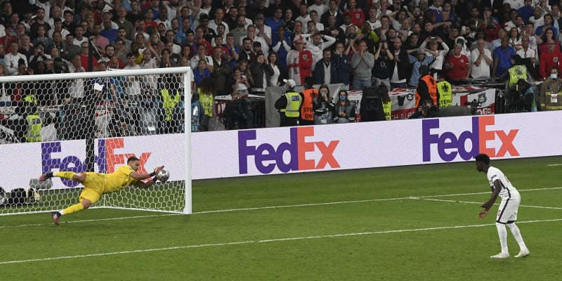 Gianluigi Donnarumma chytá pátou penaltu rozstřelu. Neúspěšný střelec Bukayo Saka už ví, že je konec.