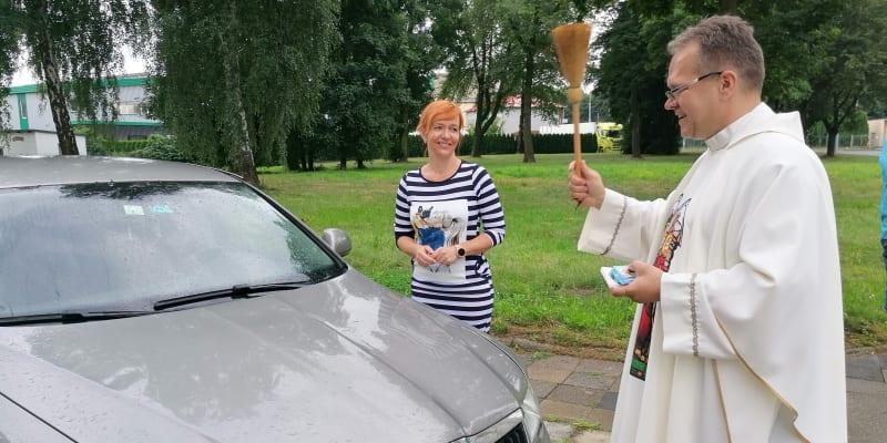 Farář Krzysztof Szewczyk světí automobily u ostravského kostela sv. Františka a Viktora v Hrušově.