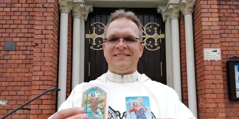 Farář Krzysztof Szewczyk se svatými obrázky s modlitbou ke sv. Kryštofovi