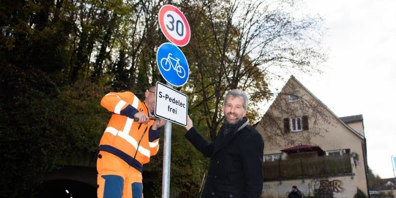 Starosta města Tübingen Boris Palmer pózuje u montáže značky před novým tunelem určeným pro cyklisty a elektromopedy.
